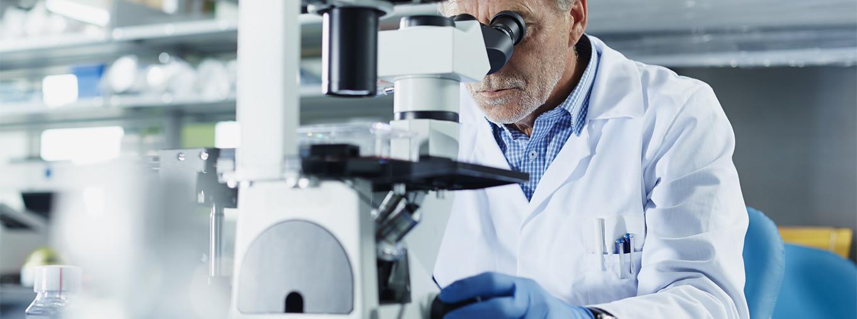 Un médecin regarde dans un microscope